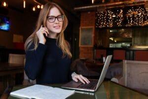 Arbeitende Frau am Handy und Macbook